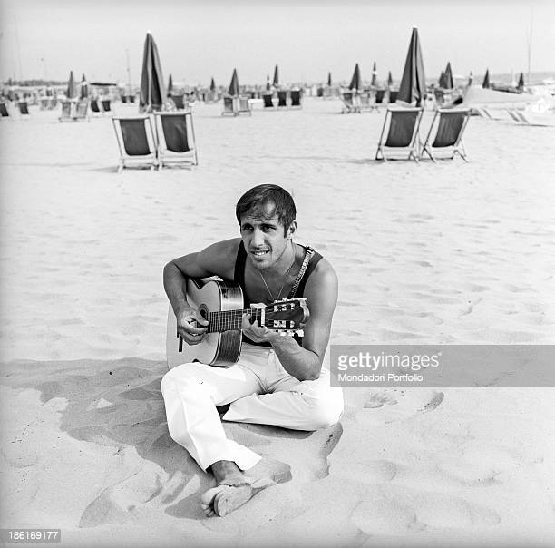 Italian singer and actor Adriano Celentano playing the guitar sitting at the beach Versilia August 1967