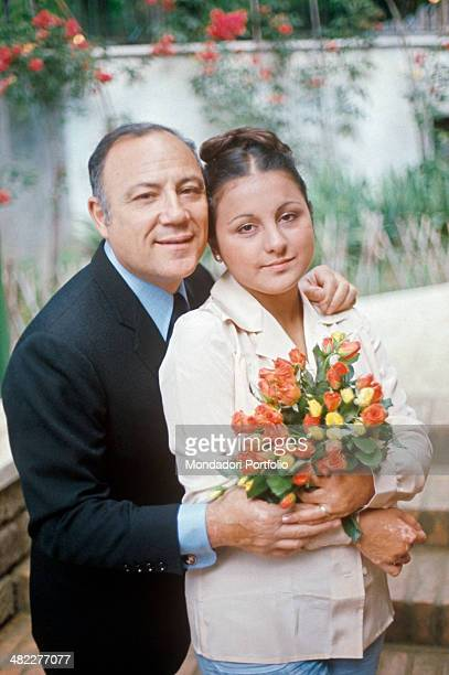 Italian singer and actor Claudio Villa hugging his Italian wife Patrizia Baldi holding a bunch of flowers 1975