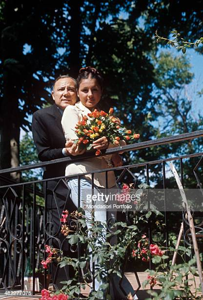 Italian singer and actor Claudio Villa posing his Italian wife Patrizia Baldi holding a bunch of flowers 1975