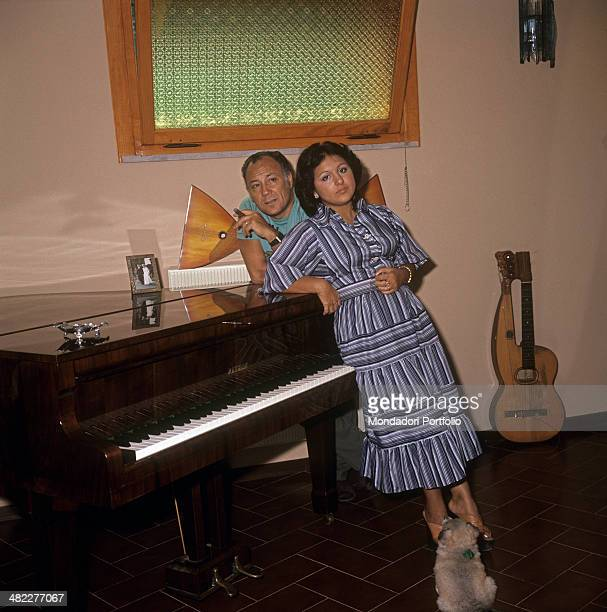 Italian singer and actor Claudio Villa posing leaned on a piano beside his Italian wife Patrizia Baldi 1975