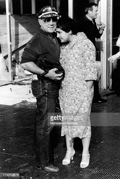 Italian singer and actor Claudio Villa with a puppy in his arms hugging his wife Patrizia Baldi Rome 1979