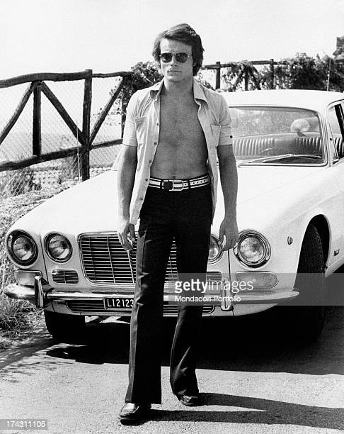 Italian singer and actor Massimo Ranieri posing in front of a car in the street wearing an open shirt Italy 1970s