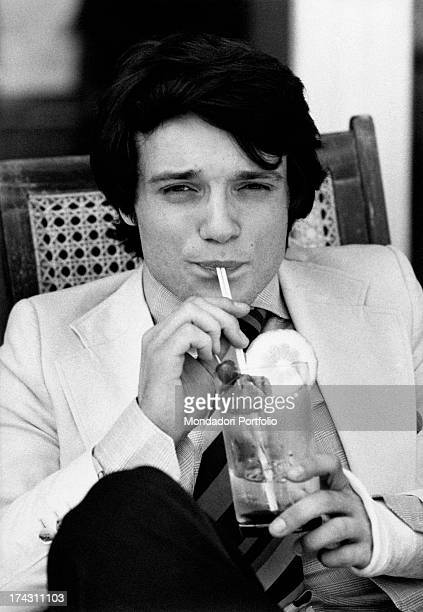 Italian singer and actor Massimo Ranieri sitting drinking a beverage Rome 1970s