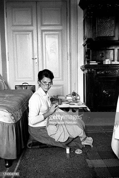Italian singer and actress Giorgia Moll sitting on the floor and sewing Rome March 1957