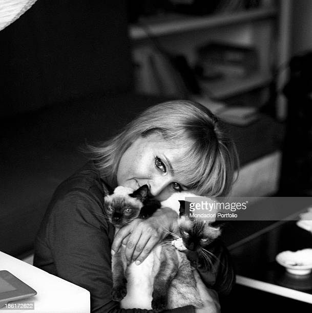Italian singer and actress Laura Betti holding and cuddling two Persian cats The actress lives in a small flat at the last floor of via Montoro 4...