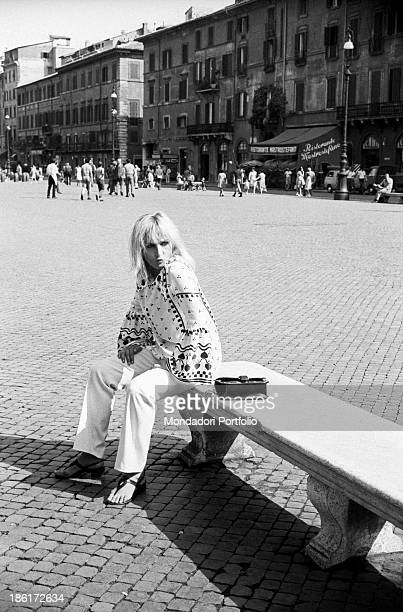 Italian singer and actress Laura Betti sitting on a bench in piazza Navona. Rome, September 1968.