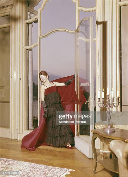 Italian singer and actress Milva posing in a livingroom of Villa Castelli in an evening dress with fur applications made by Italian dressmaker and...