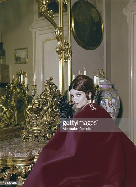 Italian singer and actress Milva posing in a livingroom of Villa Castelli in a red cape made by Italian dressmaker and fashion designer Germana...