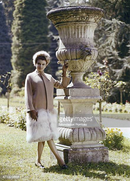 Italian singer and actress Milva posing in the garden of Villa Castelli in a pale pink coat with fur applications made by Italian dressmaker and...
