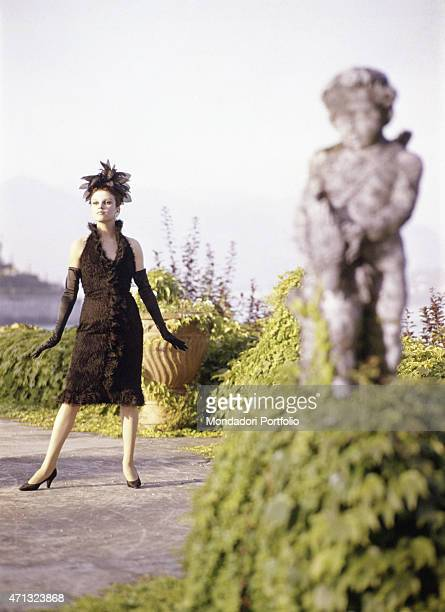 Italian singer and actress Milva posing in the garden of Villa Castelli in an elegant black dress made by Italian dressmaker and fashion designer...