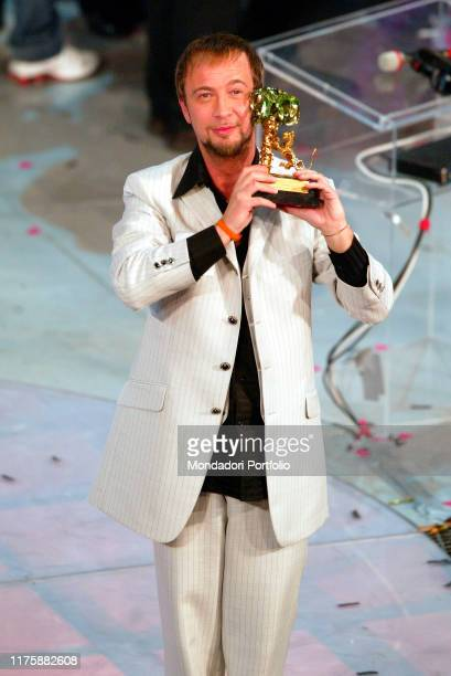 Italian singer and Festival winner Marco Masini while he holds the prize Sanremo March 6th 2004