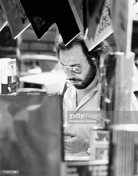 Italian singer and songwriter Antonello Venditti browsing the items on sale on a book stall Rome 1970s