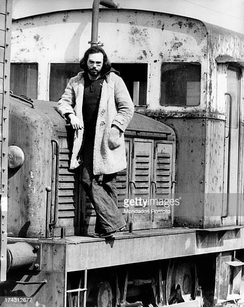 Italian singer and songwriter Antonello Venditti posing leaning against a locomotive Rome 1970s