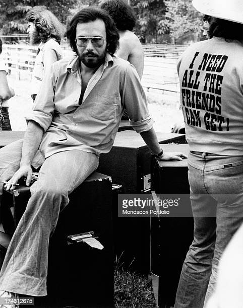 Italian singer and songwriter Antonello Venditti sitting on the equipment for a concert Beside him a man wears a Tshirt saying I need all the friends...