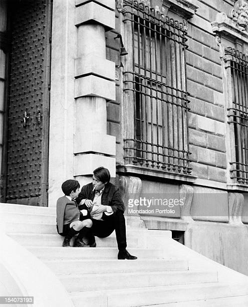 Italian singer and songwriter Fabrizio De Andre sitting on a staircase with his son Italian singer and songwriter Cristiano De Andre Genoa April 1968