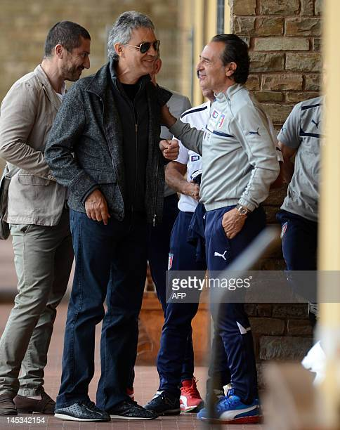 Italian singer Andrea Bocelli arrives with Italian coach Cesare Prandelli for a national football team training session in Coverciano on May 27 2012...