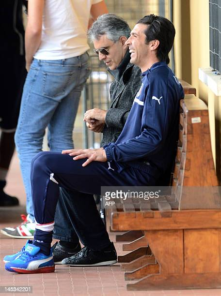 Italian singer Andrea Bocelli sits with Italian player GianLuigi Buffon during a national football team training session in Firenze on May 27 2012...