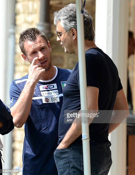 Italian singer Andrea Bocelli speaks with player Antonio Cassano a national football team training session in Firenze on May 27 2012 AFP...