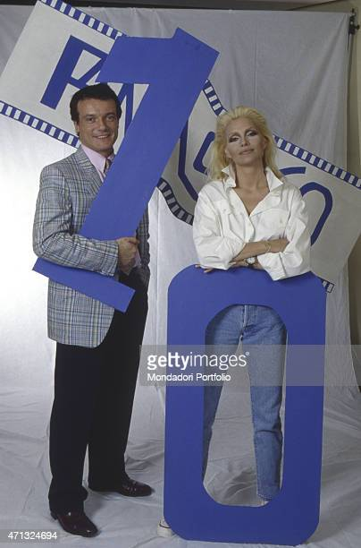 Italian singer Anna Oxa and Italian singer and actor Massimo Ranieri posing beside two big numbers The artists present the TV variety show Fantastico...