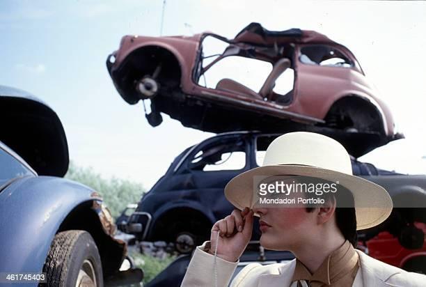 Italian singer Anna Oxa posing wearing makeup near some demolished cars 1978