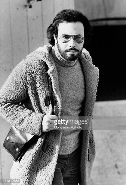 Italian singer Antonello Venditti wearing a fur and a shoulder bag Rome 1970s