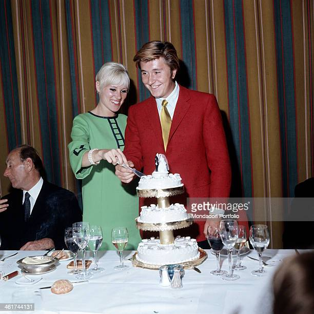 Italian singer Bobby Solo born Roberto Satti wearing a red jacket and a gilded tie with his wife the French dancer Sophie Teckel who wears a...