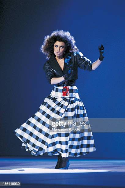 Italian singer Loredana Berté dancing wearing a long tartan skirt and a red camera at her wrist 1986