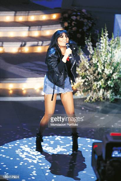 Italian singer Loredana Berté wearing a miniskirt and a leather jacket performing the song Angeli e angeli at the 45th Sanremo Music Festival Sanremo...