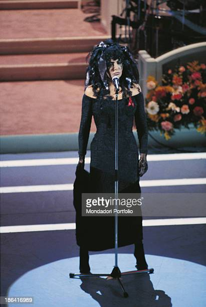 Italian singer Loredana Berté wearing a wig and a red ribbon symbolizing the war against AIDS pinned on her dress performing the song Amici non ne ho...