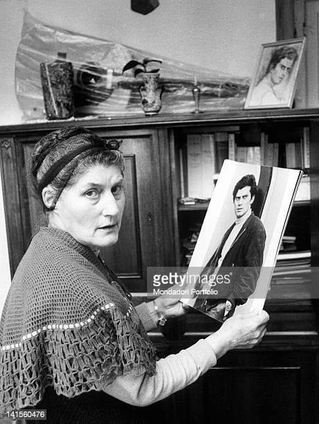 Italian singer Luigi Tenco's mother holding her son's portrait