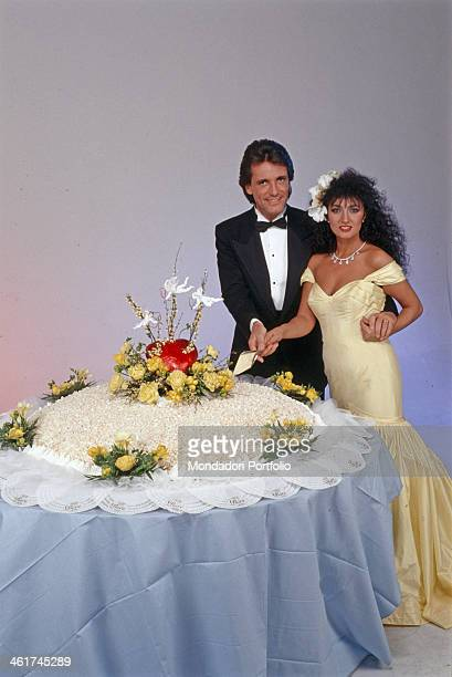 Italian singer Marcella Bella and Mario Merello newlyweds cutting the wedding cake Italy 1989