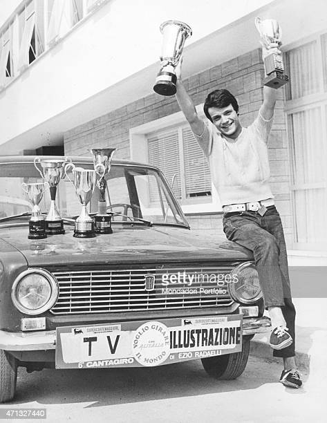 Italian singer Massimo Ranieri leaning on a car bonnet and lifitng up some awards in a photo shooting at the 6th Cantagiro that he won in the B round...