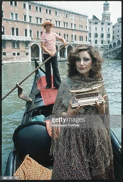 Italian singer Mia Martini on a gondola holding the Gondola d'Oro prize won at the Mostra Internazionale di Musica Leggera with the song Donna Sola...