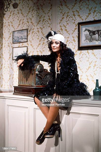 Italian singer Mia Martini posing leaning on an old cash till wearing a 1920s dress 1975