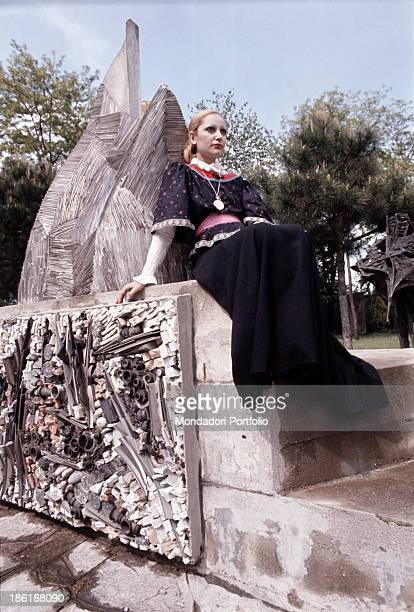 Italian singer Mia Martini posing seated beside a monument 1972
