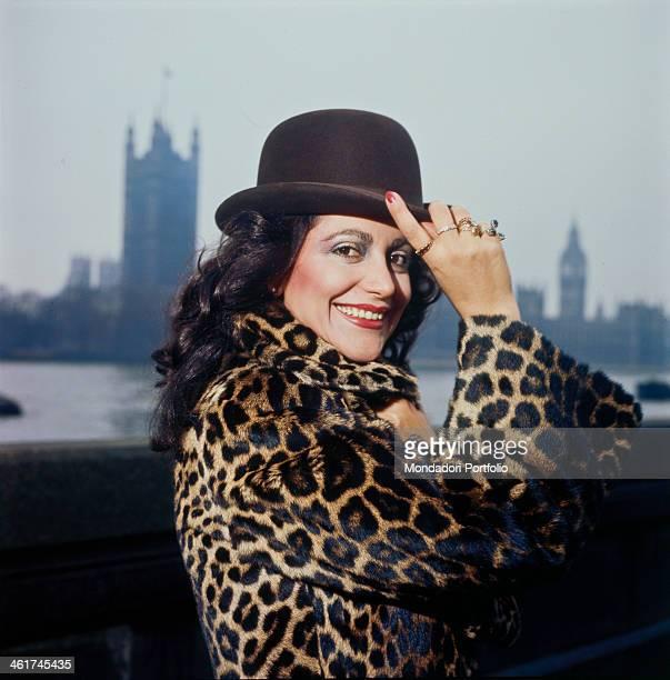 Italian singer Mia Martini posing smiling wearing a leopardskin fur coat and a bowler hat London 1977