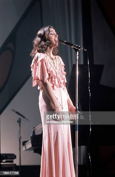 Italian singer Mia Martini singing a song beside a piano wearing a pink dress 1970s
