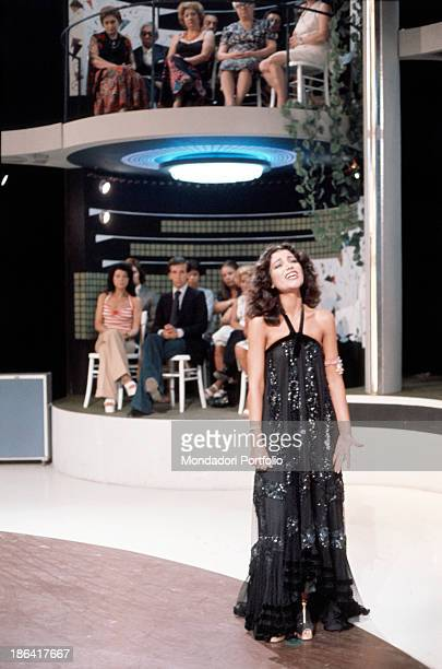 Italian singer Mia Martini singing a song wearing a long black dress trimmed with rhinestones 1975
