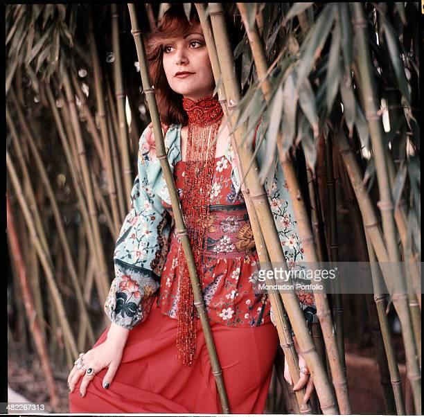 Italian singer Mia Martini sitting next to some ditch reeds 1973