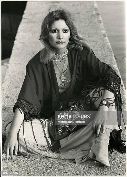 Italian singer Mia Martini sitting on a low wall Viareggio 1970s