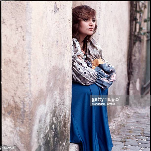 Italian singer Mia Martini sitting on a step with her arms crossed 1973