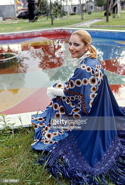 Italian singer Mia Martini smiling crouched in front of a pool 1972