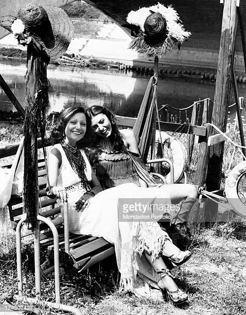 Italian singer Mia Martini smiling sitting on a swing chair with her sister Italian singer Loredana Bertè Rome 1970s