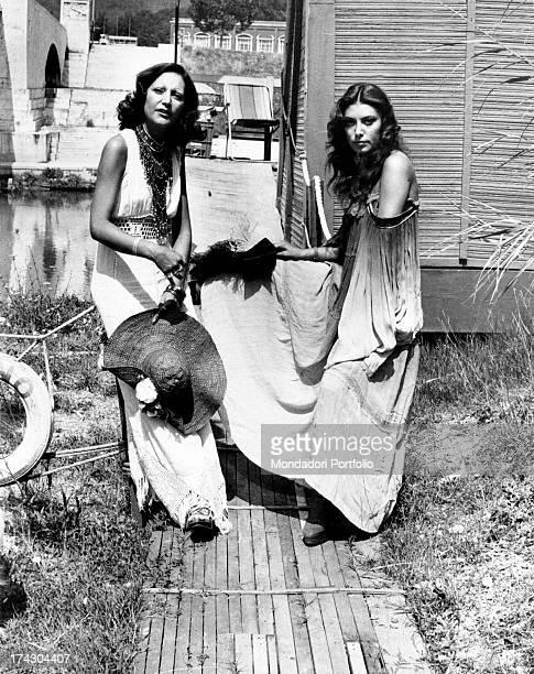 Italian singer Mia Martini with her sister Italian singer Loredana Bertè posing near a house by a river Rome 1970s