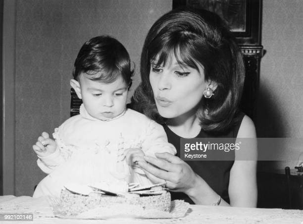 Italian singer Milva helps her daughter Martina celebrate her first birthday with a cake 1964
