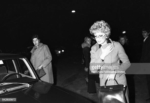 Italian singer Mina and Italian director Antonello Falqui getting in a car. 1970s
