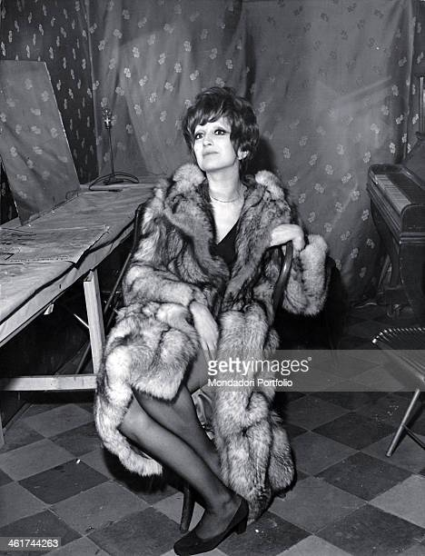 Italian singer Mina born Mina Anna Maria Mazzini sits on a chair in the middle of a small room with a plank and a piano on the background she wears a...