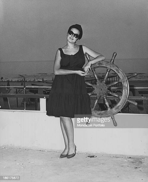 Italian singer Mina posing leaned against a steering wheel on the terrace of the night club La Bussola Le Focette 1965