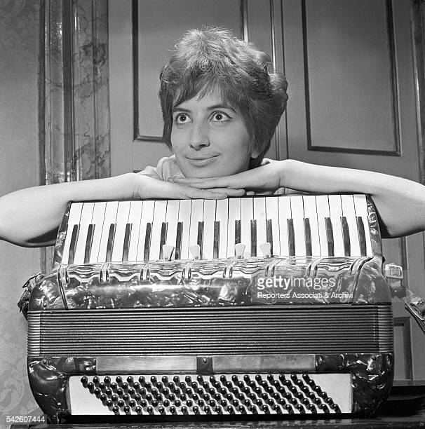 Italian singer Mina posing with an accordion 1960