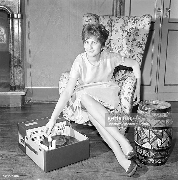 Italian singer Mina sitting in an armchair using a record player 1960